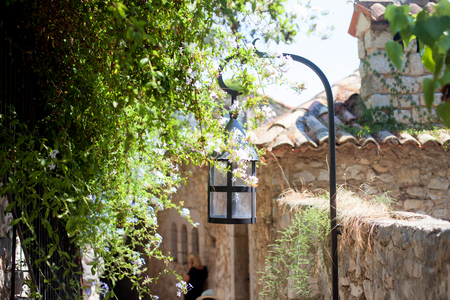 to the other side: Street lamp in a village in France with a green tree on the other side, summertime