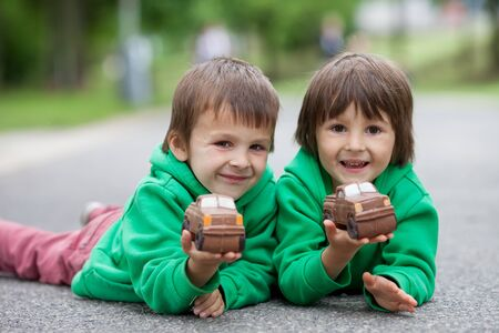 chocolaty: Funny little boys playing with car of chocolate, outdoor, having fun