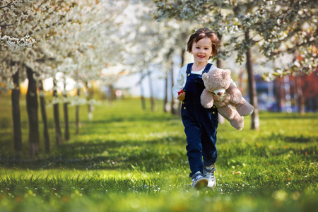 bear berry: Cute little boy, eating strawberry in the park on a spring sunny afternoon, together with his big teddy bear