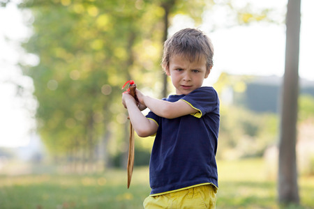 glaring: Angry little boy, holding sword, glaring with a mad face at the camera, outdoors in the park Stock Photo