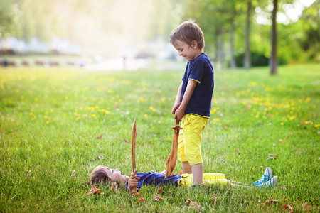 sibling rivalry: Two little boys, holding swords, glaring with a mad face at each other, fighting outdoors in the park