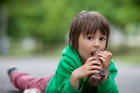 chocolaty: Funny little boy playing with car of chocolate, outdoor, having fun