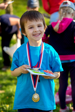 kindergarden: Proud preschool boy, holding prizes and medals after annual sport kindergarden competition