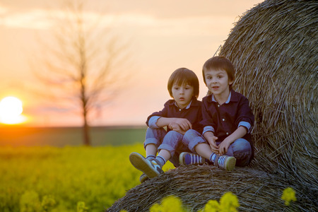 oilseed: Two children, boy brothers in a oilseed rape field, sitting on a bale of haystacks, watching the sunset Stock Photo