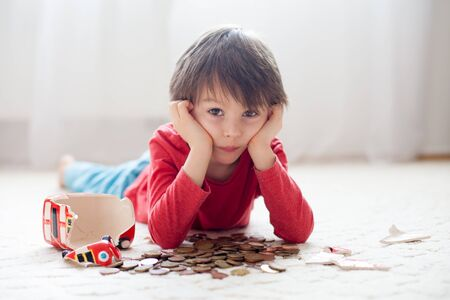emptying: Little boy, breaking his piggy bank, emptying all saved money to buy gift for mothers day