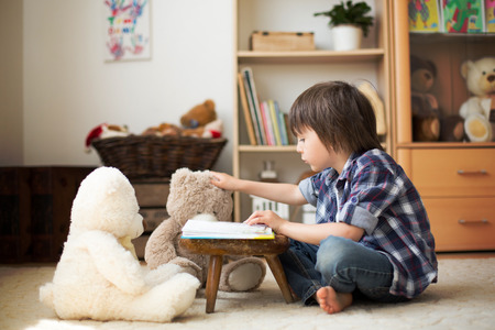 coming home: Cute little child, preschool boy, reading a book to his teddy bears at home, sun rays coming through window, dust in the air Stock Photo