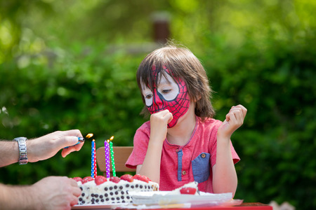 five years old: Cute five years old boy, celebrating his birthday in the park, face painted as spider Stock Photo