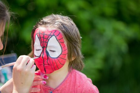 five years old: Cute little five years old boy,. having his face painted as spider on his birthday party Stock Photo