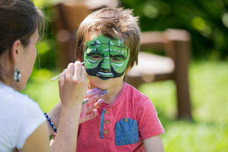 five years': Cute little five years old boy,. having his face painted on his birthday party, outdoors
