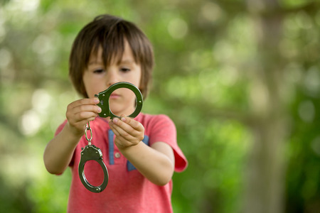 cuffs: Cute little boy with the hand cuffs on his hands, playing
