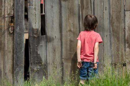 Schattige kleine jongen met de handboeien op zijn handen, het spelen Stockfoto