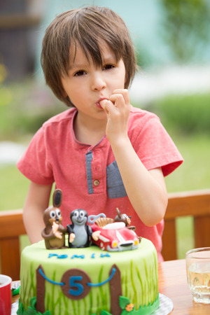birthday party kids: Beautiful adorable five year old boy, celebrating his birthday, blowing candles and eating the cake, outdoors. Birthday party for kids