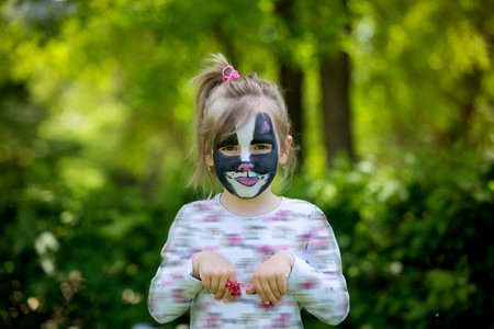 five years old: Cute little five years old girl, having her face painted as kitten on her birthday party, outdoors