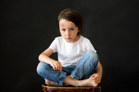 unworried: Little sad boy with big bump on his head from fall. Preschool boy, banged his head when falling, isolated on black Stock Photo