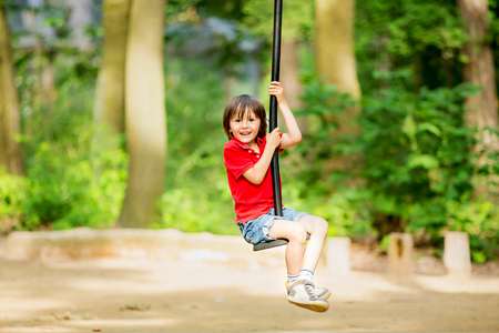 playground rides: Cute child, boy, rides on Flying Fox play equipment in a childrens playground