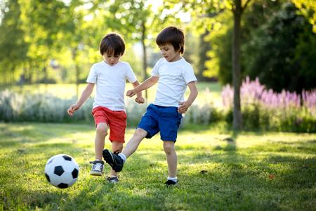 サッカーを一緒に 2 つのかわいい小さな子供、夏。屋外サッカーを遊んでいる子供たち