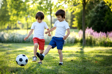 Two cute little kids, playing football together, summertime. Children playing soccer outdoor Archivio Fotografico