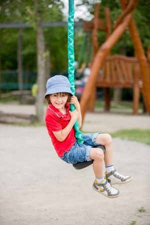 playground rides: Cute child, boy, rides on Flying Fox play equipment in a childrens playground, summertime