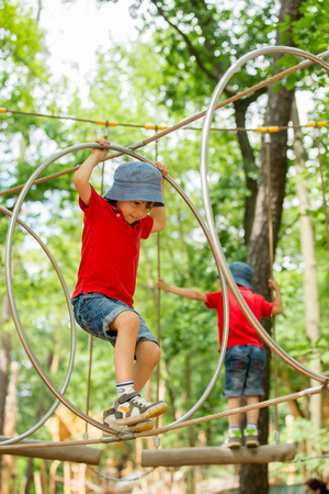 Cute child, boy, climbing in a rope playground structure, springtime Stock Photo