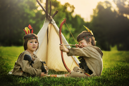 Cute boys dressed in traditional native american costume playing outdoors in the park with bow, arrows and hatchet