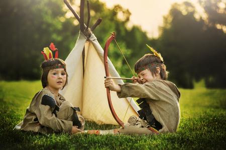 Retrato lindo de los niños americanos nativos con trajes, jugando al aire libre en el parque con arco, flechas y hacha en la puesta del sol, el verano Foto de archivo