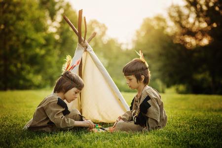 Retrato lindo de los niños americanos nativos con trajes, jugando al aire libre en el parque con arco, flechas y hacha en la puesta del sol, el verano Foto de archivo - 60295793