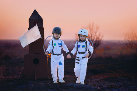 imagining: Two adorable children, boy brothers, playing in park on sunset, dressed like astronauts, imagining they are flying on the moon Stock Photo