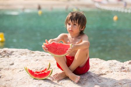 poquito: Un lindo y pequeño niño, muchacho, come la sandía en la playa, el verano Foto de archivo