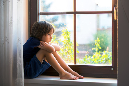 unprotected: Sad child, boy, sitting on a window shield, watching the sunset Stock Photo