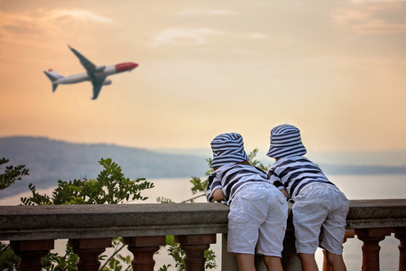 pretend: Two little children, boy brothers, looking at landing airplane in the sky over the sea on sunset and dreaming of becoming a pilots Stock Photo