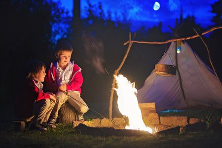 Two sweet boys, sitting around the campfire after sunset, listening scary stories