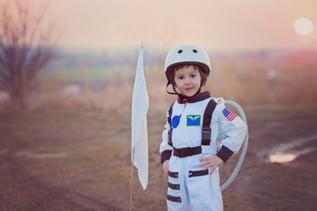 Adorable little boy, dressed as astronaut, playing in the park with rocket and flag, dreaming about becoming an astronaut Stock Photo