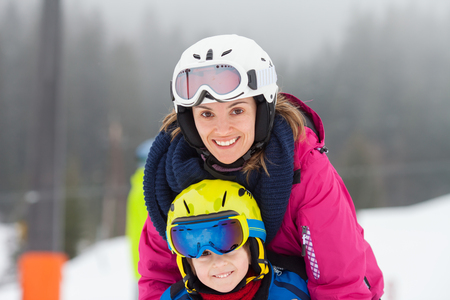 kids at the ski lift: Sweet young boy and his mother, learning to ski on a mild ski slope in Austrian ski resort on a cloudy day Stock Photo