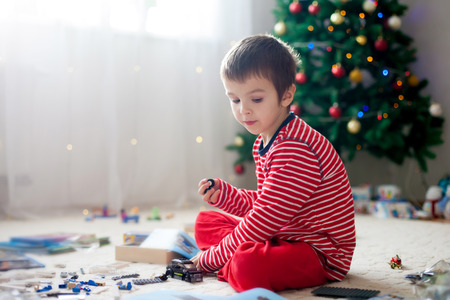 Two sweet children, boy brothers, opening presents on Christmas day, still in pajamas. Kids happiness