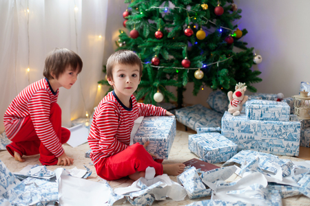 Two sweet children, boy brothers, opening presents on Christmas day, still in pajamas. Kids happiness Stock fotó