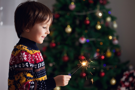 Beautiful Little child holding burning sparkler on New Years Eve, casual clothing, bengal fire Stock Photo