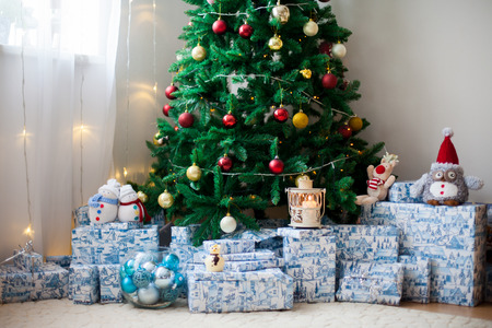 christmas tree presents: Christmas tree with lots of presents under the tree, lights and toys, candles, living room