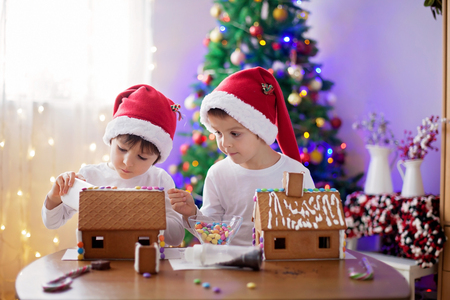 ginger bread man: Two sweet boys, brothers, making gingerbread cookies house, decorating at home in front of the Christmas tree, child playing and enjoying, Christmas concept Stock Photo