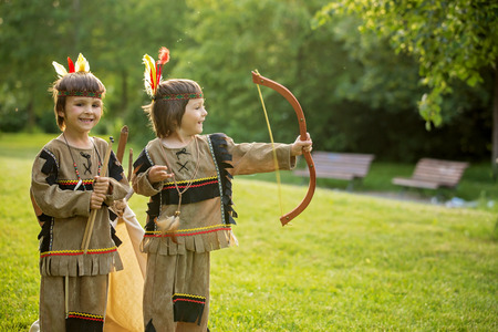 hatchet man: Cute portrait of native american boys with costumes, playing outdoor in the park with bow, arrows and hatchet on sunset, summertime