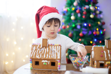 cute house: Cute little boy, making gingerbread cookies house, decorating at home in front of the Christmas tree, child playing and enjoying, Christmas concept