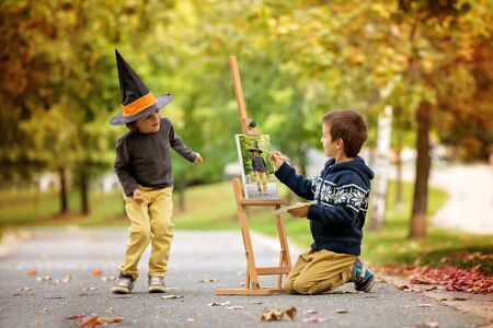 Two sweet children, boy brothers, having fun painting in autumn park together. One child paint the other kid, dressed for halloween