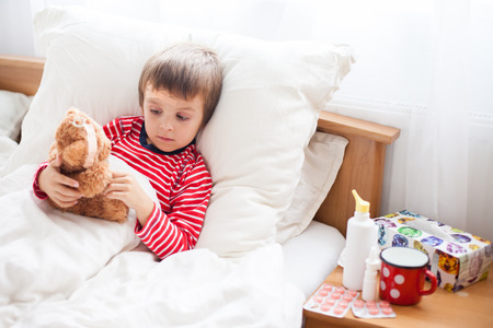Sick child boy lying in bed with a fever, holding terry bear with bandage  , resting Stock Photo