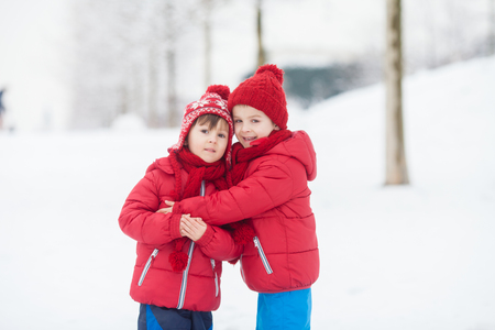 Two adorable children, boy brothers, playing in a snowy park, holding hands and hugging
