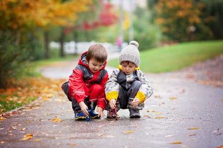 sibling rivalry: Two children, playing together with toys in the park on a rainy day, autumn time Stock Photo
