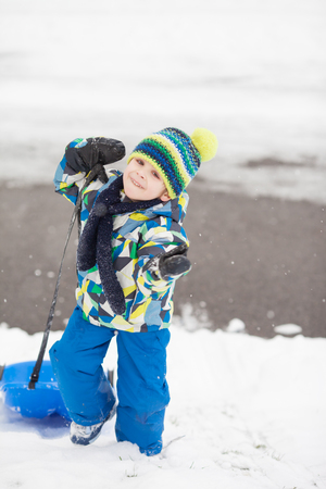Sweet little child, boy, sledging in the snow winter time, having fun