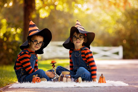 chandelier  kids: Two children, boy brothers in the park with Halloween costumes, having fun
