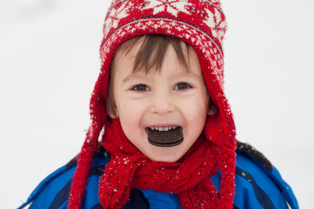 having fun in winter time: Sweet little child, boy, eating cookie in the snow winter time, having fun Stock Photo