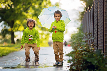 Two adorable little boys with umbrella in a park on a rainy day, playing and jumping, smiling, talking together, autumntime Stock Photo