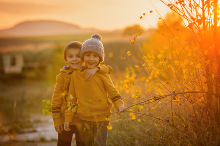 Two adorable children, having fun on sunset, making funny faces and dancing on a small rural path Reklamní fotografie