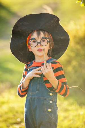 chandelier  kids: Cute little boy, playing with halloween costume in the park on sunset Stock Photo